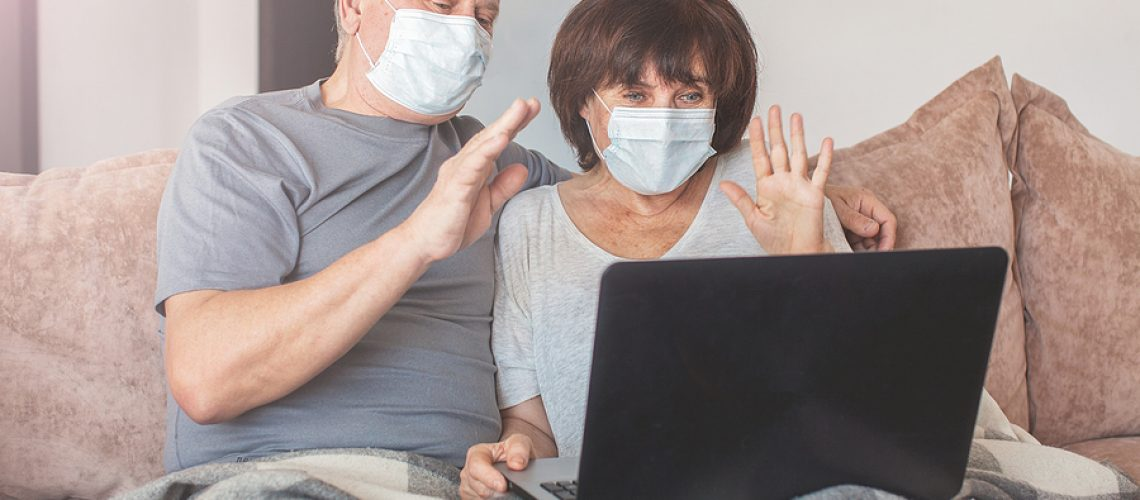 Couple old aged senior people at home with seasonal winter cold illness communicate online sit down on the sofa. Elderly couple in medical masks during the pandemic Coronavirus CoVid-19