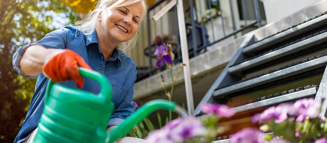 Senior woman watering plants in her garden