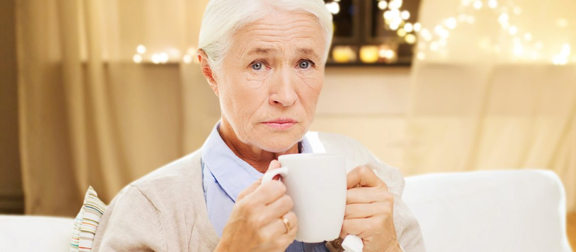 health, old age and people concept - sick senior woman suffering from flu or cold with paper napkin drinking hot tea at home over garland lights background